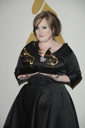 Adele holding 2 awards
