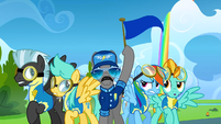 A pony holds up the blue team flag S3E07